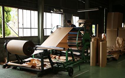 工場内① 巨大なロール紙が機械にセットされている